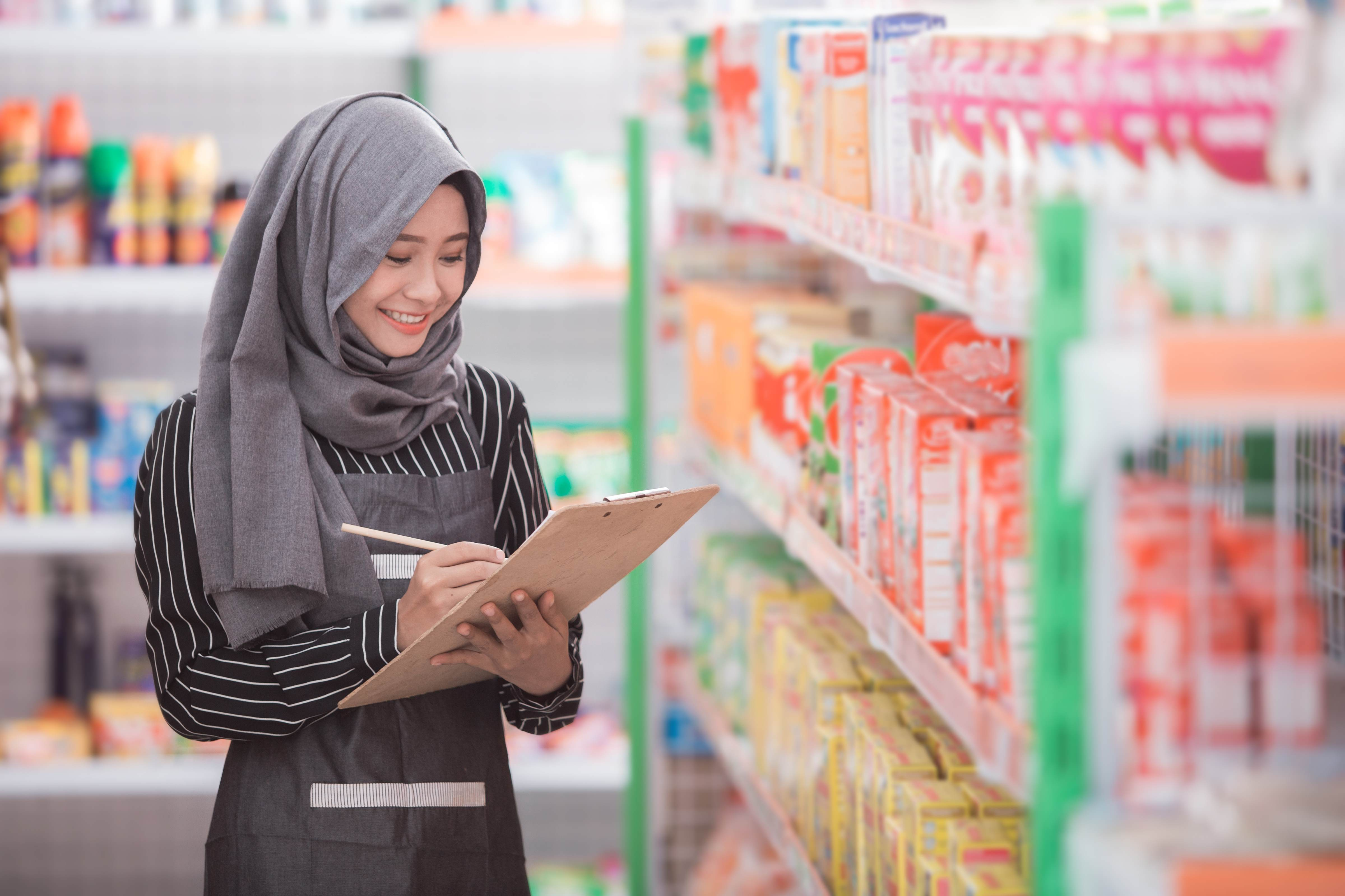 Beautiful Female wearing a headscarf looking at products on shelves in a shop. Croda has many products that are compliant with Halal Product Assurance law in Indonesia.