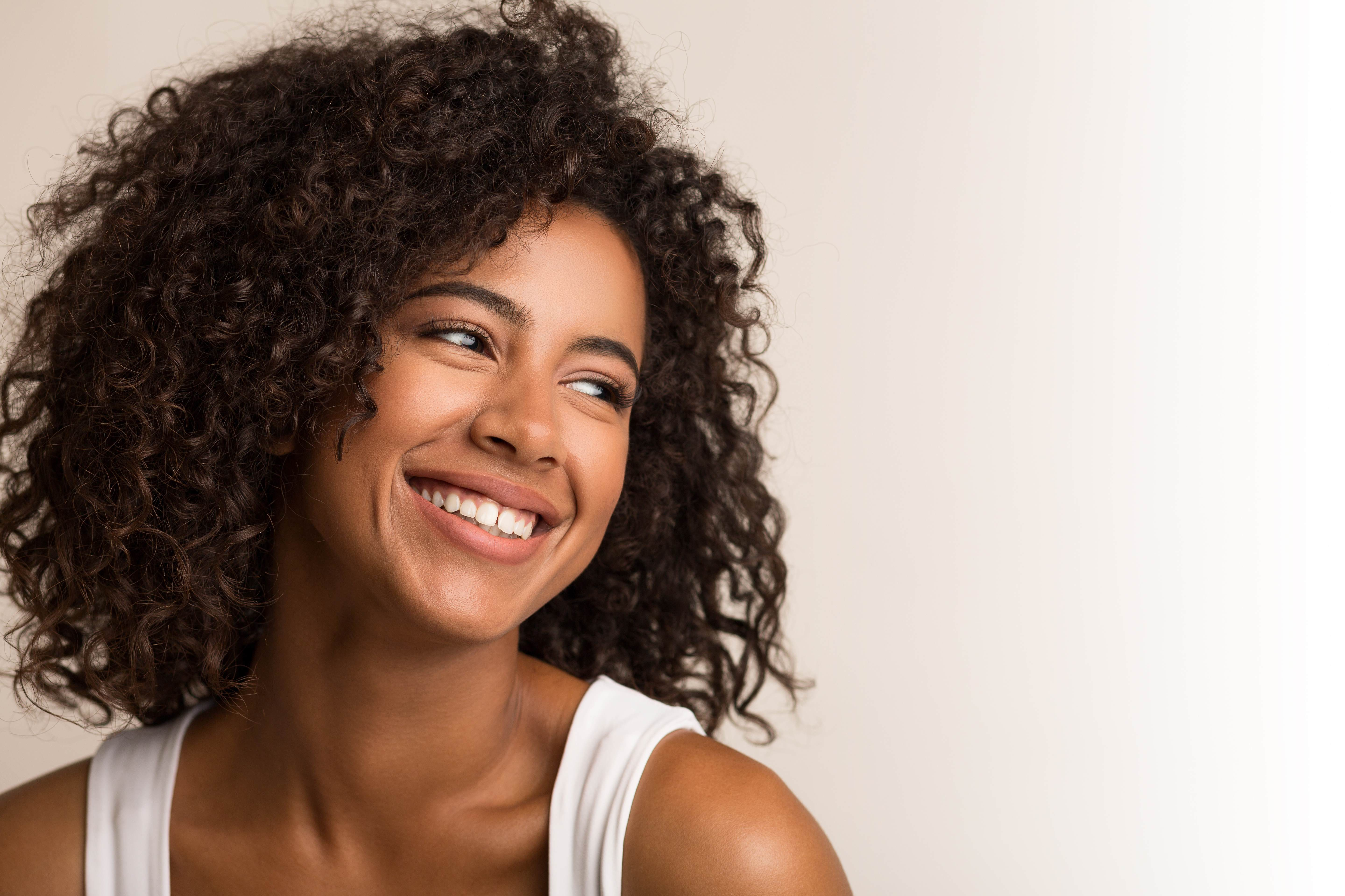 Woman smiling with curly hair and glowing skin