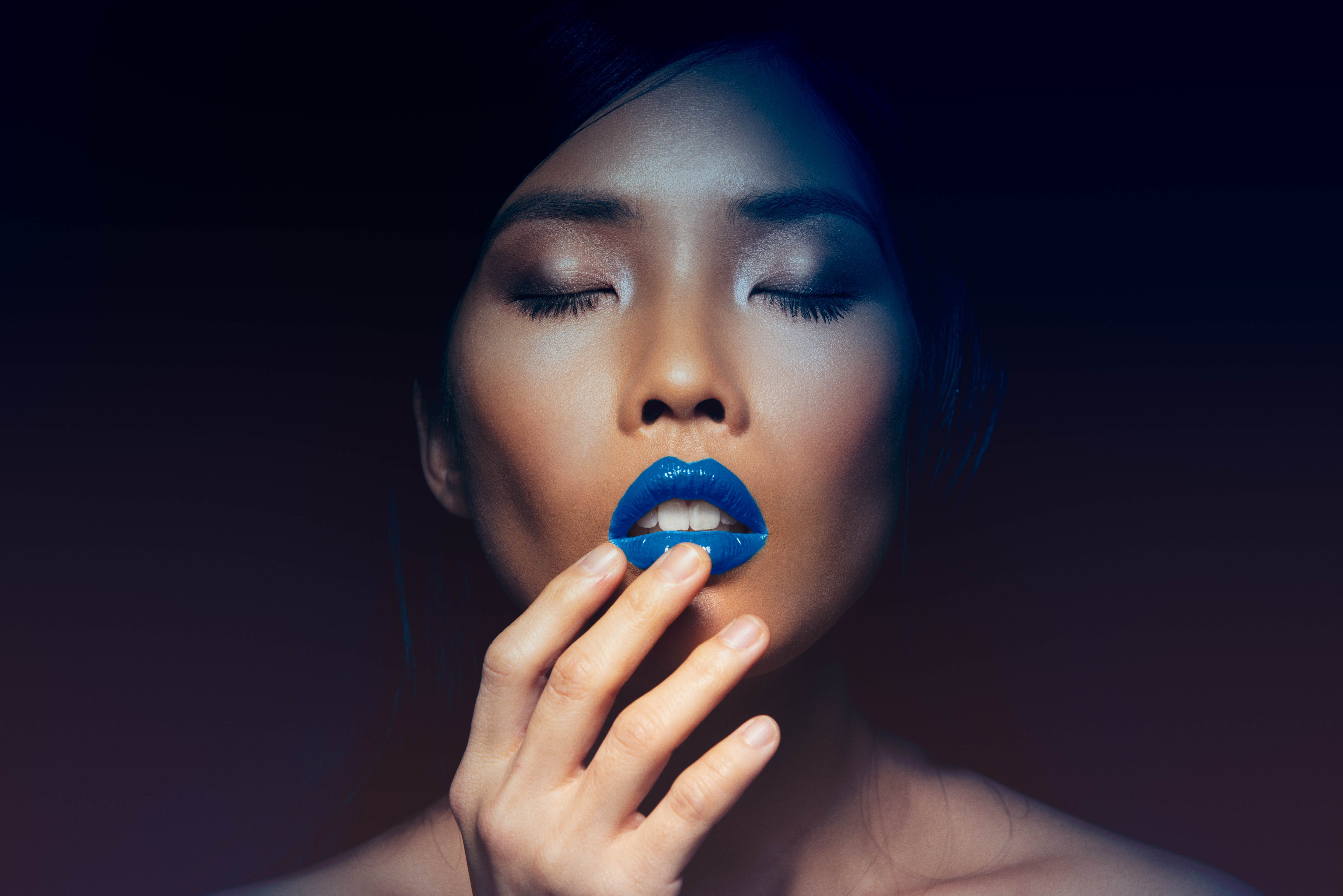 Beautiful woman on black background wearing Pantone colour of the year classic blue lipstick