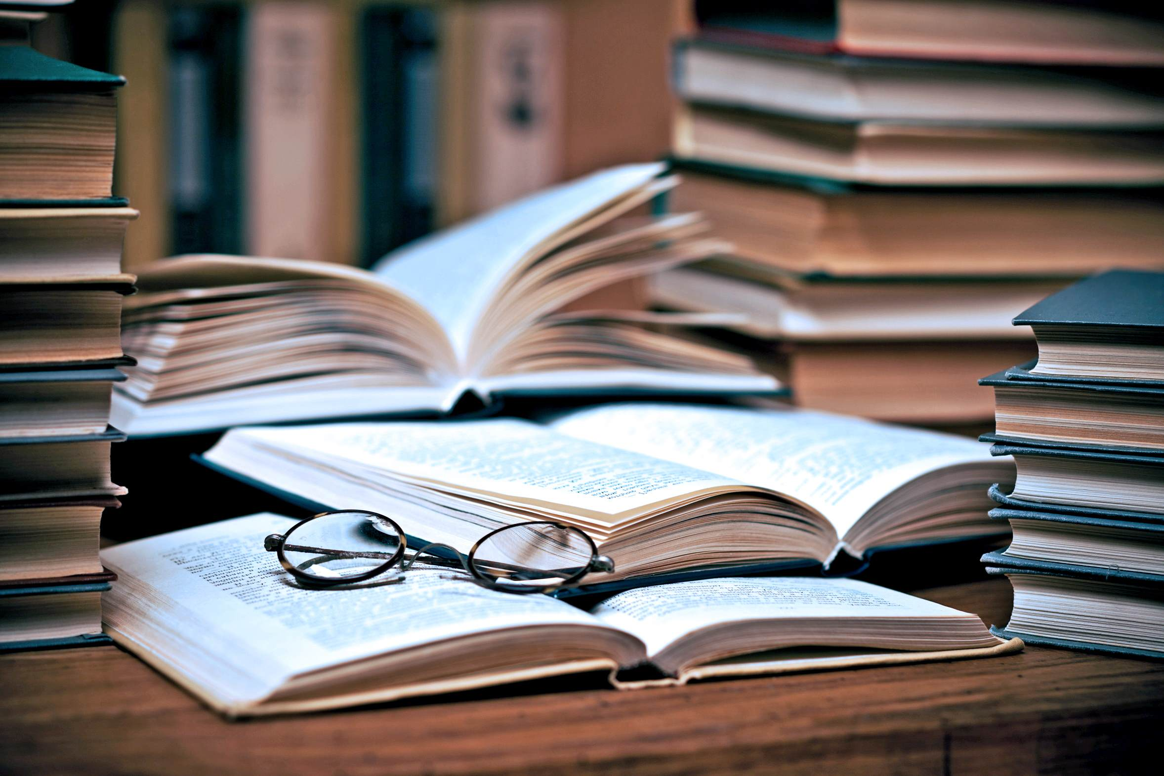 Glasses on the opened book surrounded by stack of books