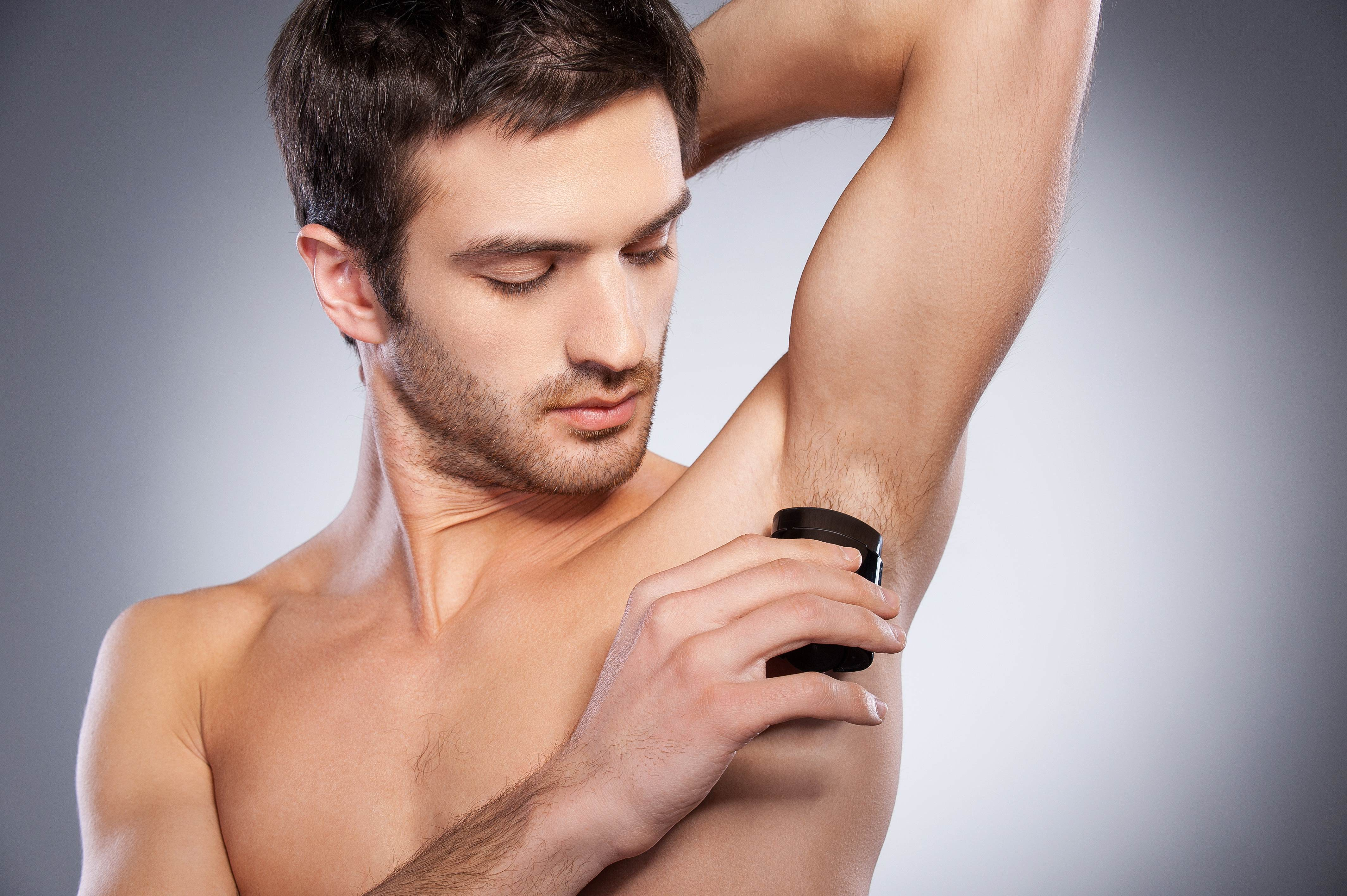 Male applying antiperspirant deodorant to his underarms showing how Croda's ingredients are effective in creating formulations in different formats including aerosol sprays, sticks, creams or roll ons