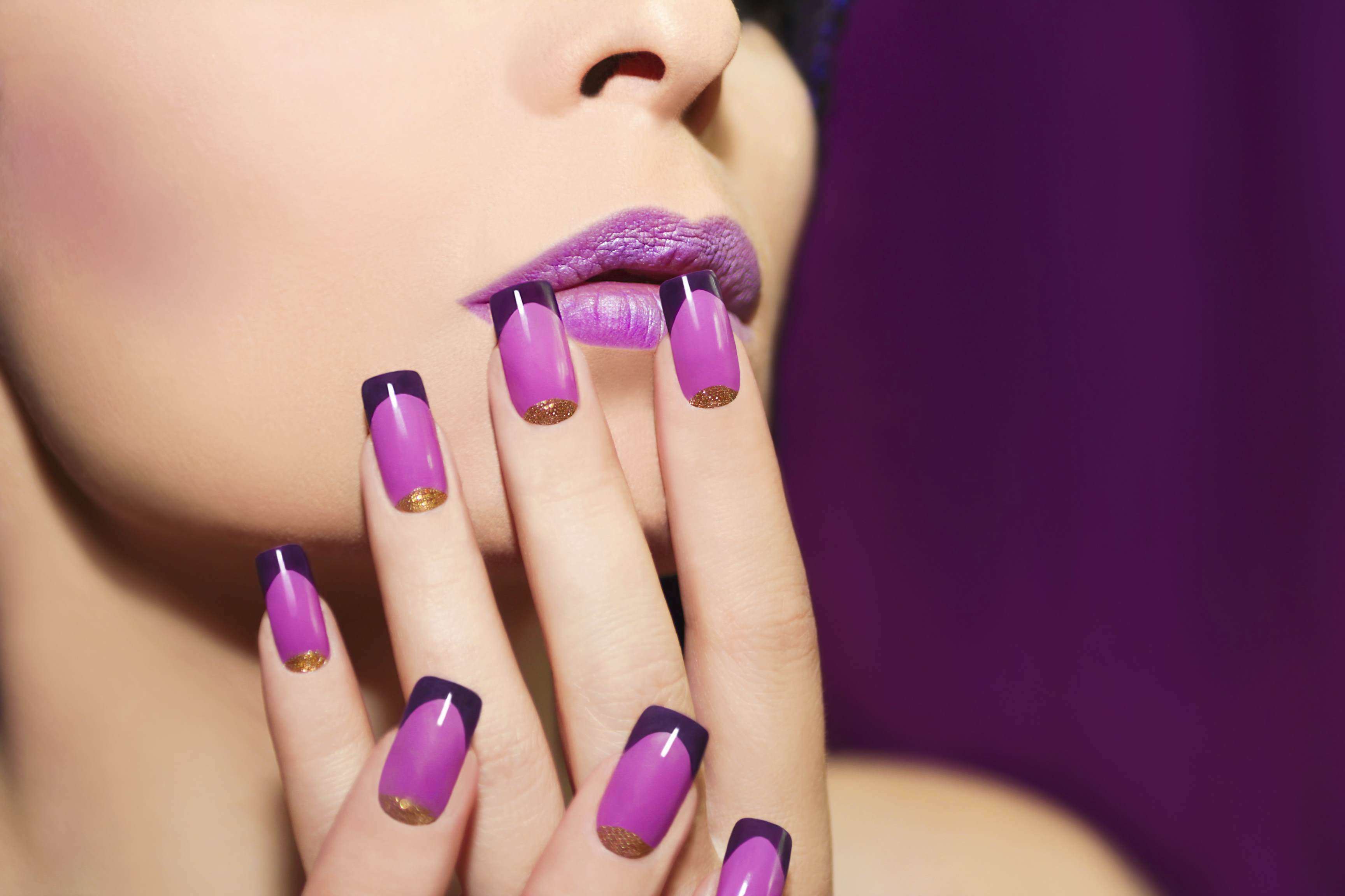Female wearing purple lipstick with purple and black french manicure and gold glitter showing how Croda's nail care ingredients can improve nail integrity, prevent damage and lock in moisture