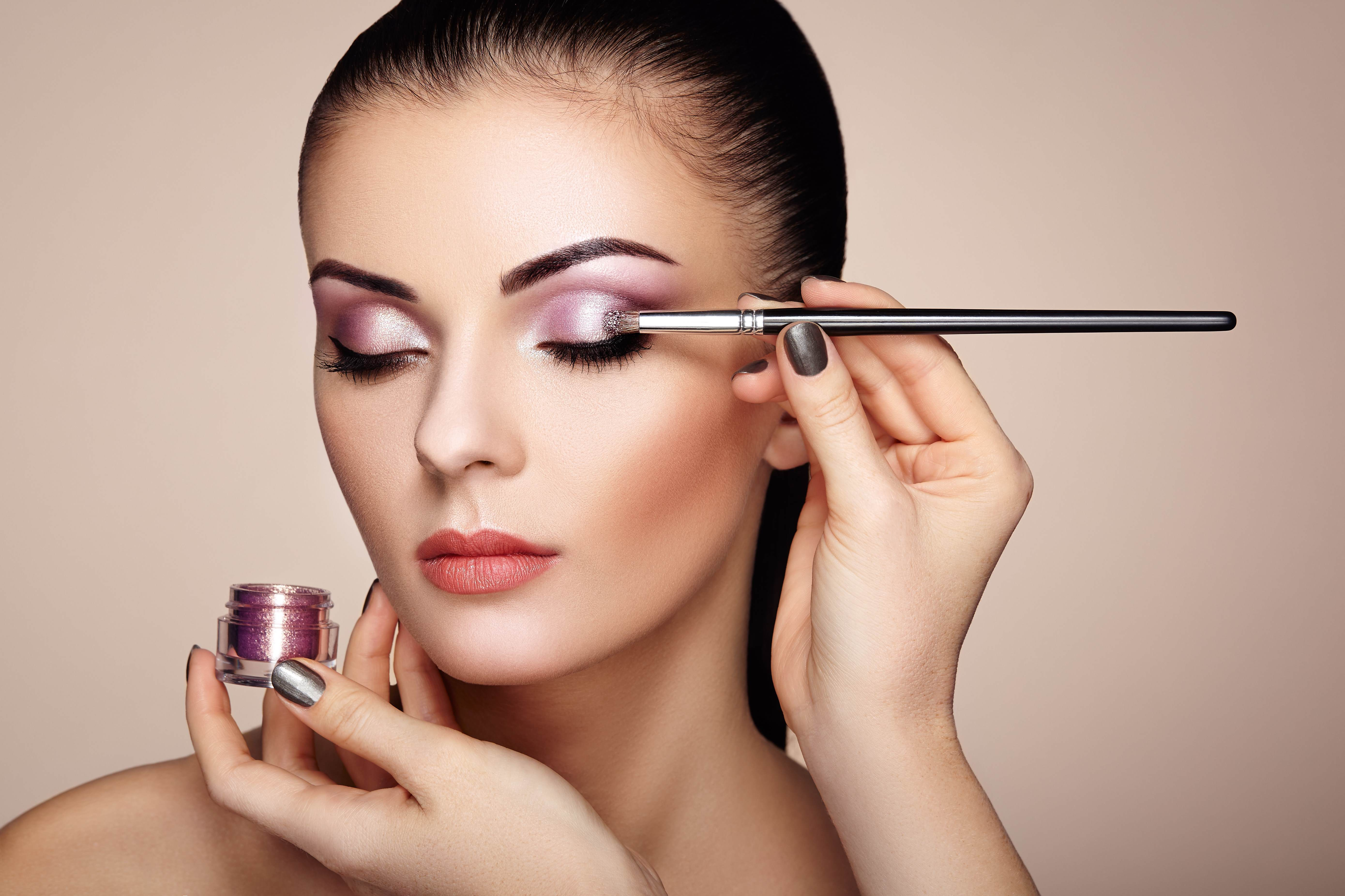 Female having purple glitter eyeshadow applied using makeup brush that showcases Croda's Moonshine effect pigment range