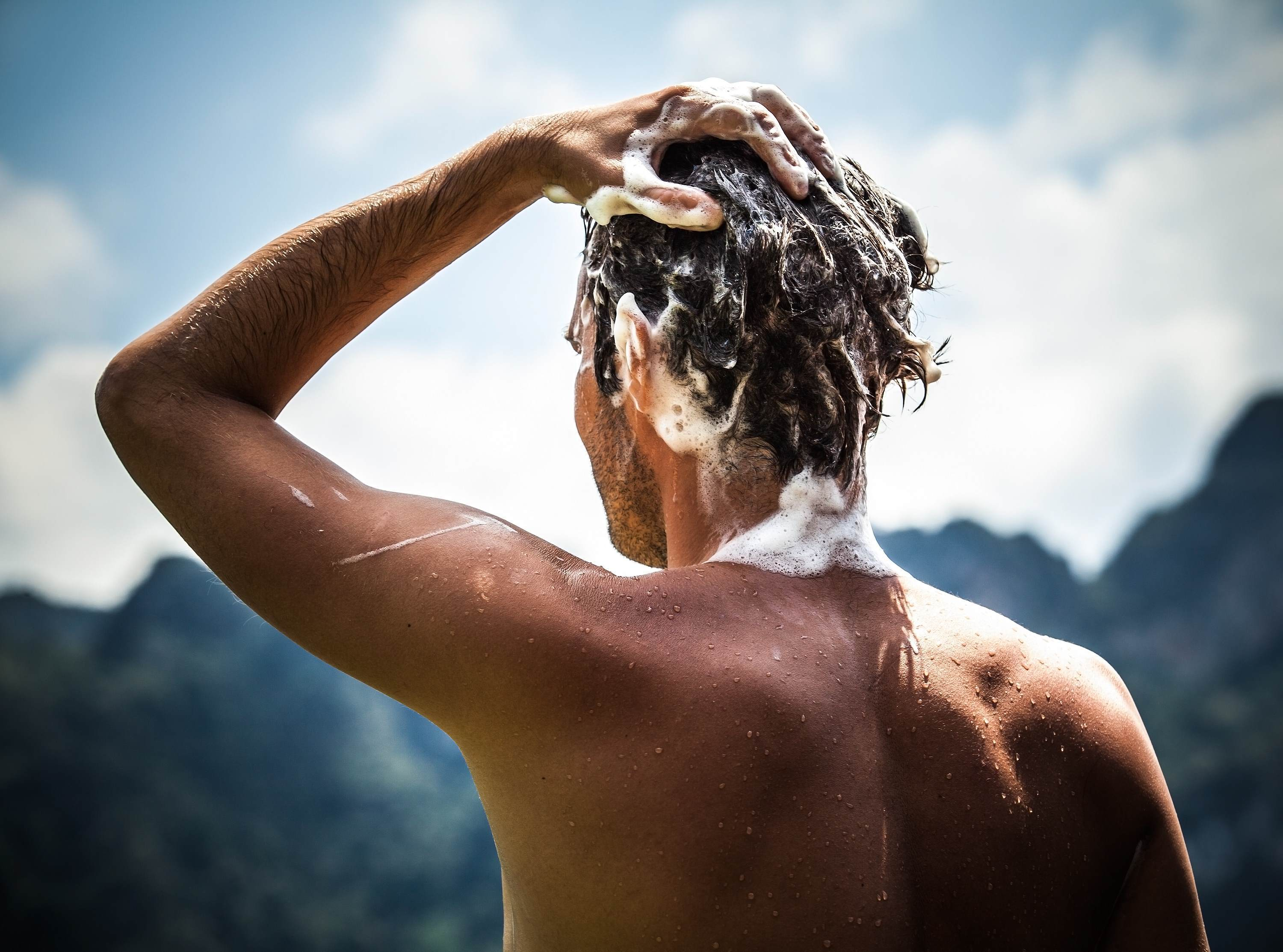 Man lathering hair with shampoo that contains Croda's diverse portfolio of ingredients for a range of hair applications ranging from scalp care, conditioning, colouring, damage and styling to give benefits such as softening, thermal protection, frizz control, colour retention and moisturisation.