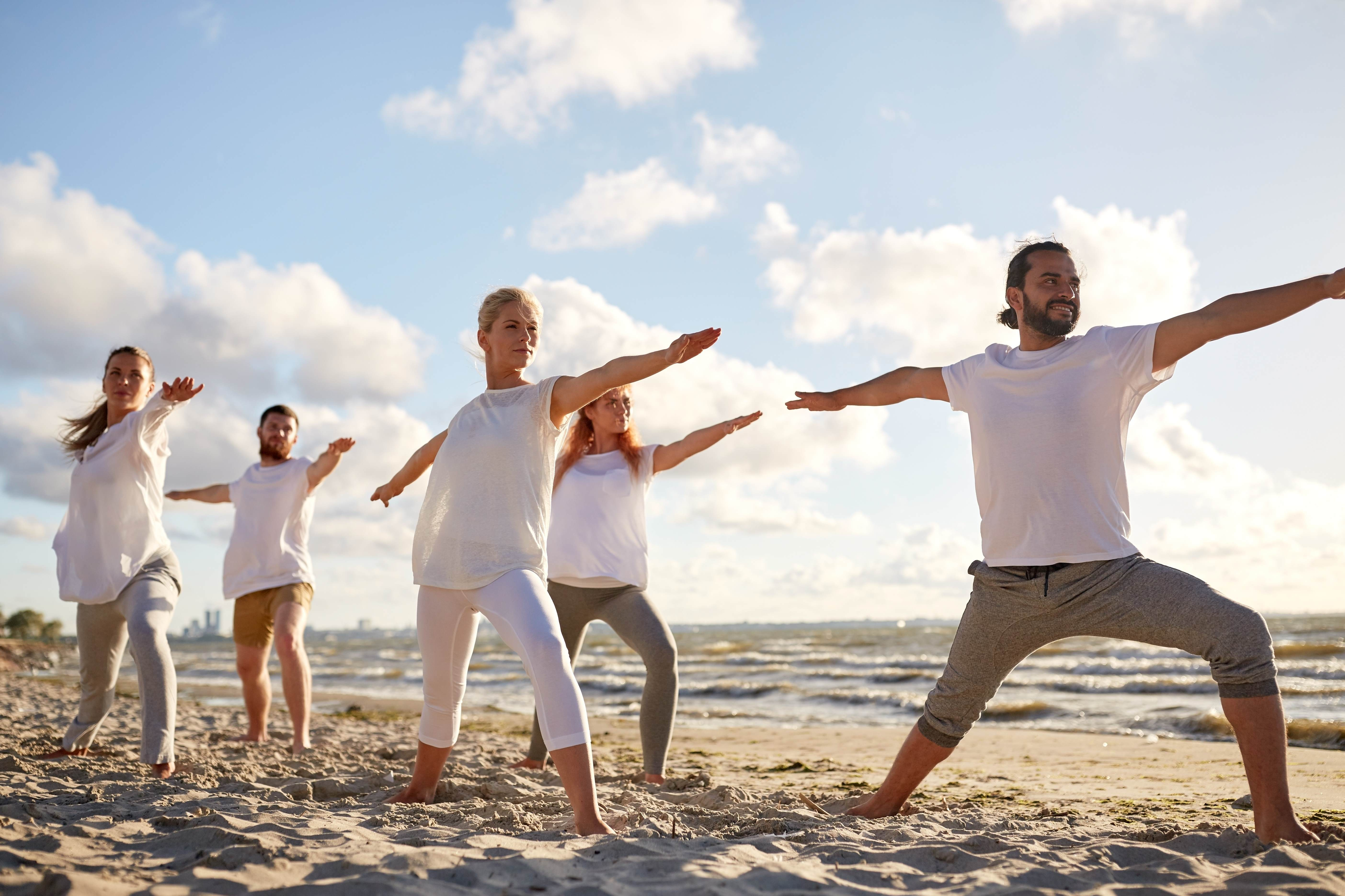 Group of men and women practising yoga at the beach in keeping with the global Active Beauty trend of body care in terms of fitness and pampering