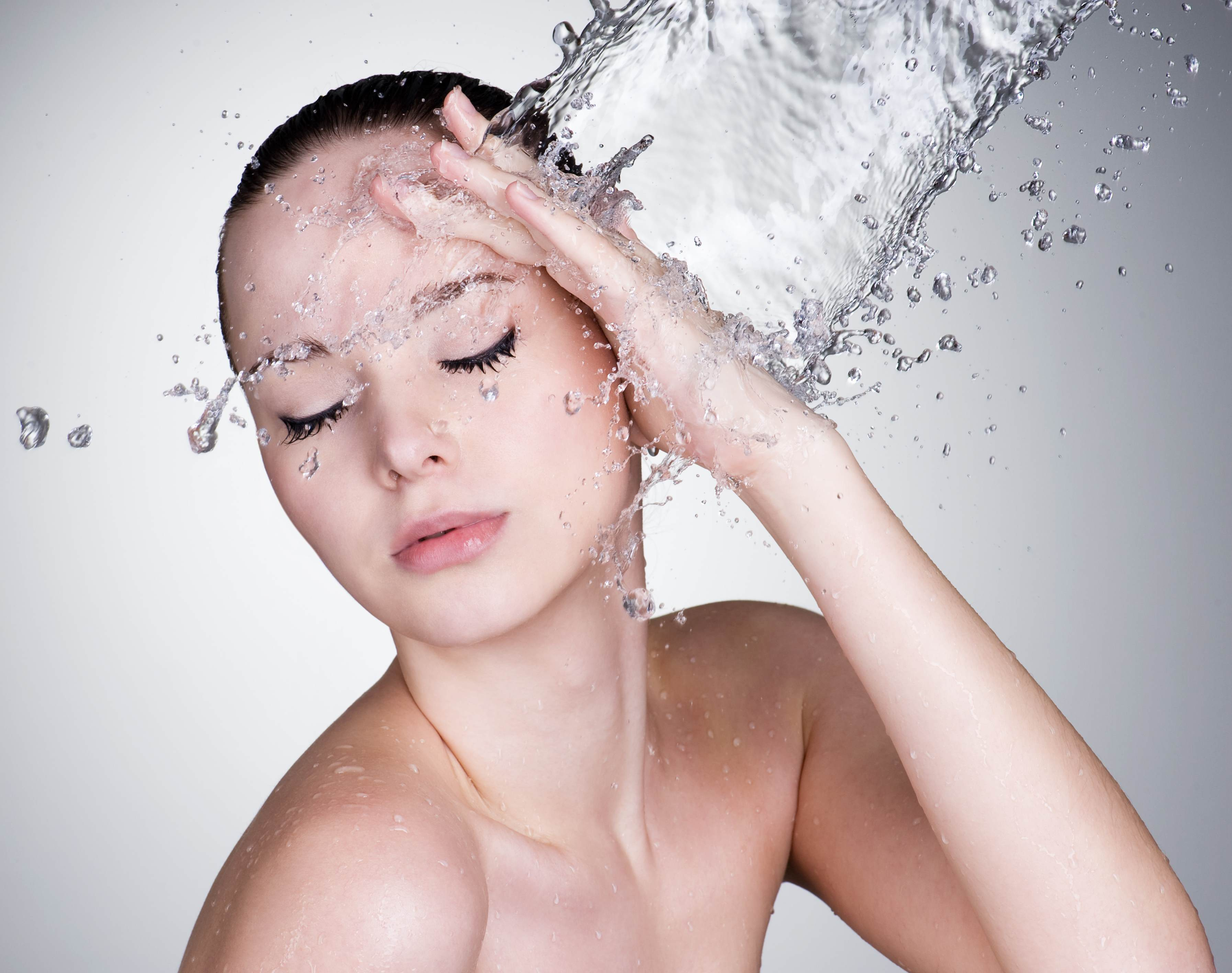 Beautiful female with water splashing on her face demonstrating effortless cleansing from Croda's range of  high performance cleansing ingredients