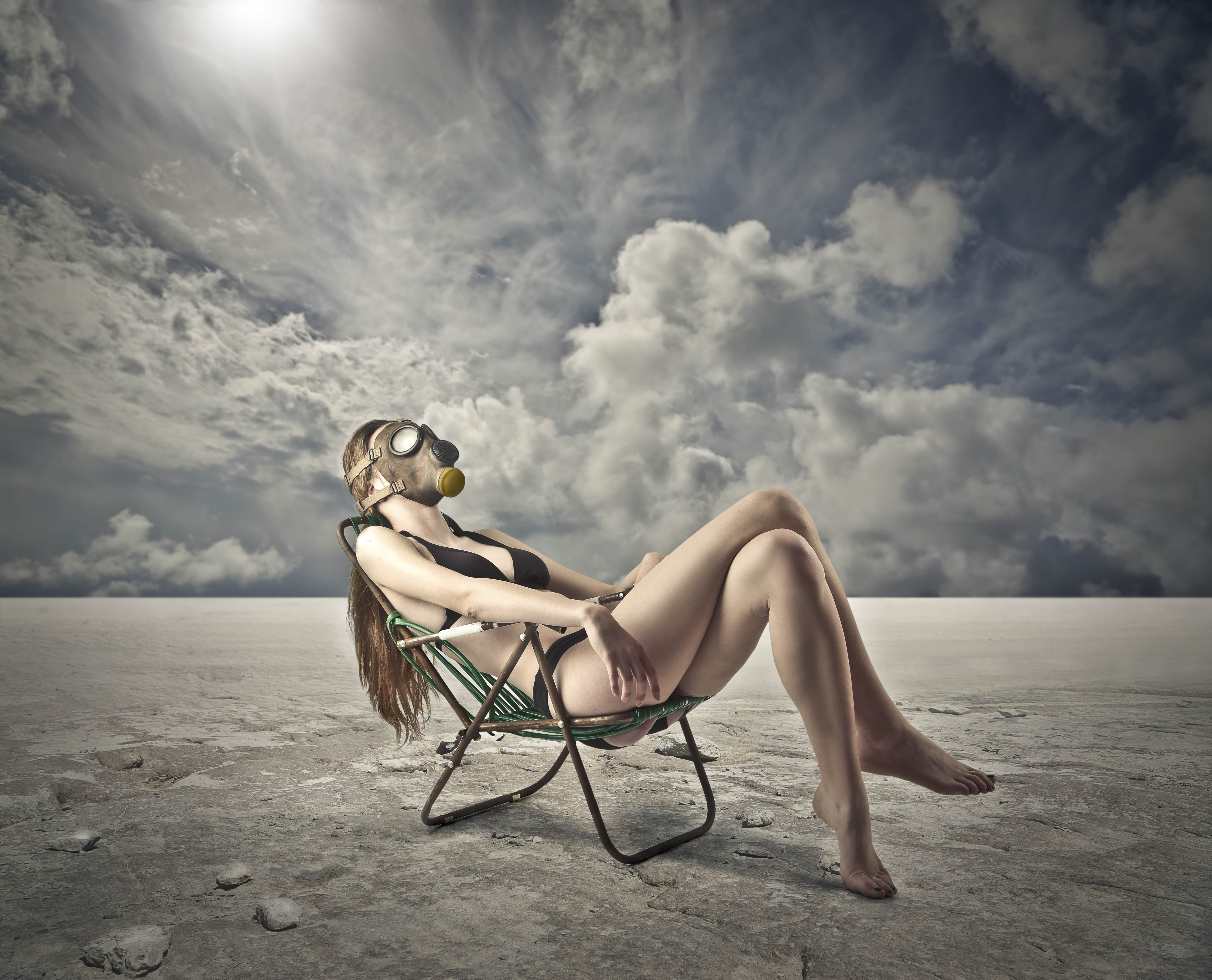 Young female wearing a black bikini and a gas mask, sitting in a deckchair sunbathing in a polluted environment where the skin is exposed to numerous pollutants that damage cells which can be protected with Croda's diverse ingredients ranges