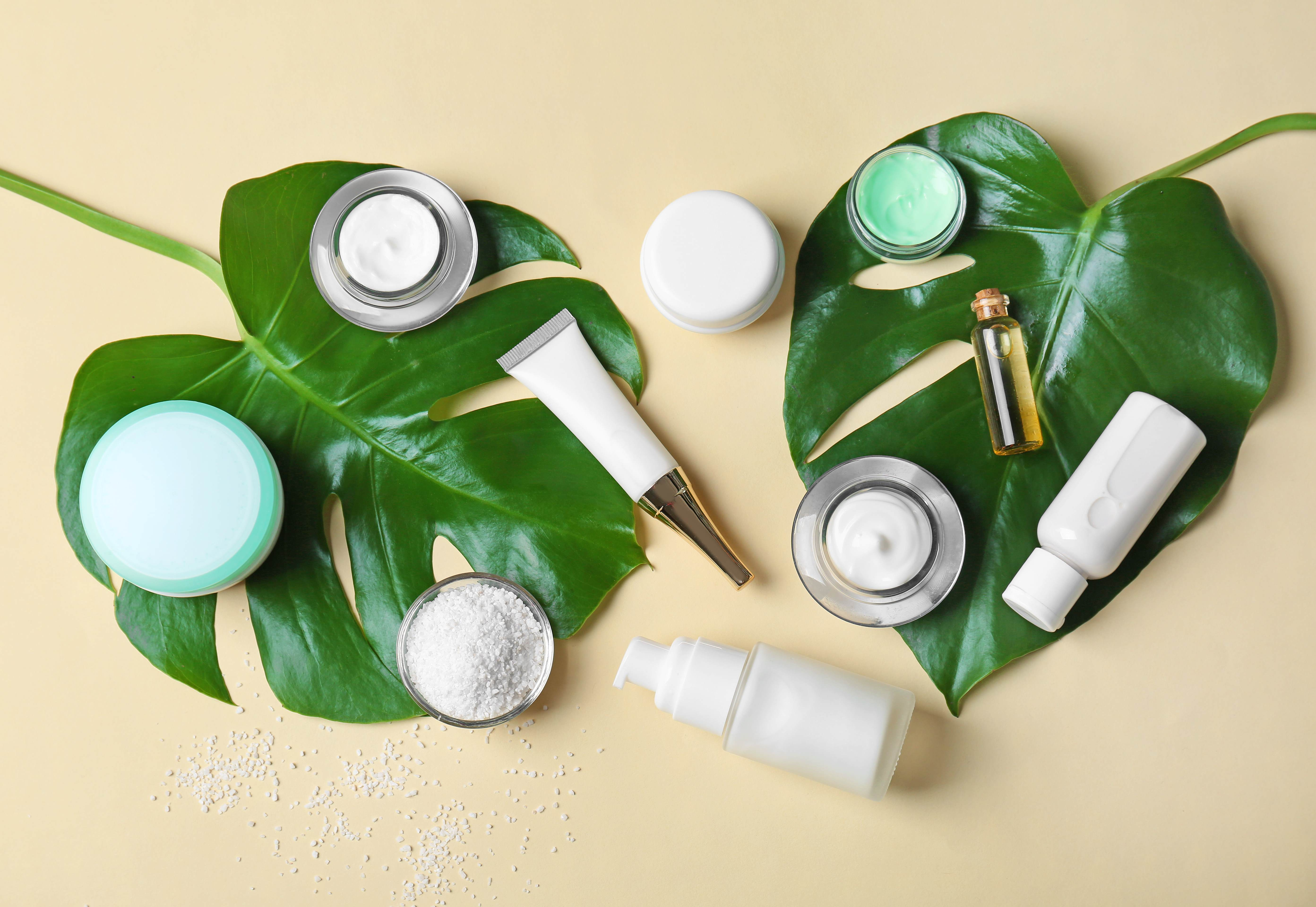 Personal care products in white pots placed on two large green leaves on a yellow background